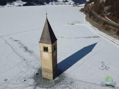 Il campanile sommerso del lago di Resia con la neve visto dal drone